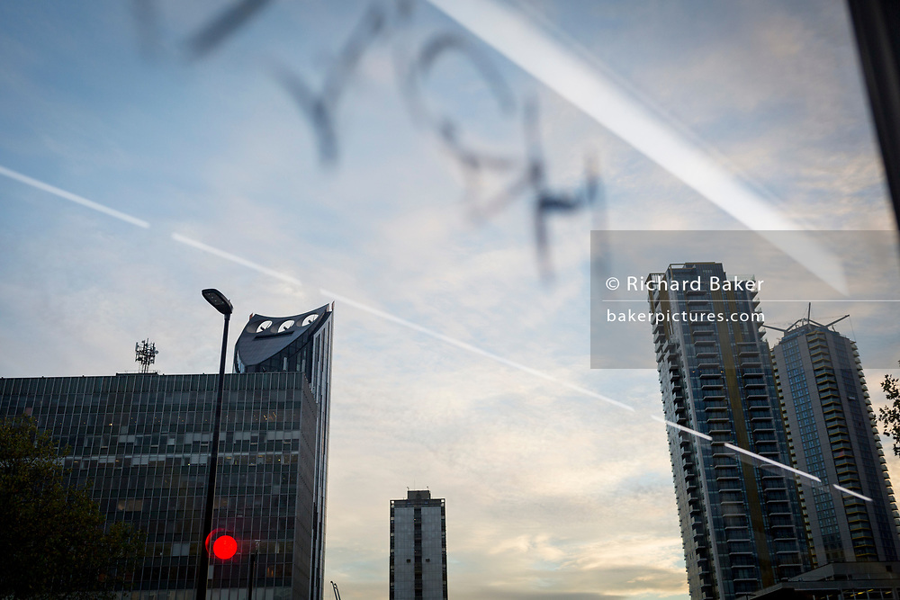 Graffiti written on the window of a London bus and urban tower blocks at Elephant & Castle, on 13th November 2017, in London, England.