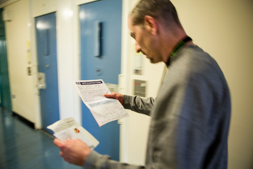 A prisoner reading the response to his application form while walking down the corridor. HMP/YOI Portland, Dorset. A resettlement prison with a capacity for 530 prisoners. Portland, Dorset, United Kingdom.
