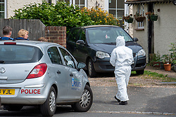 © Licensed to London News Pictures. 27/07/2021. Stoke Poges, UK. A forensic investigator outside a property on Bells Hill in Stoke Poges, Buckinghamshire, following an assault on Monday 26 July at approximately 21:30BST. A man in his twenties suffered a serious leg injury following the assault which is understood to have involved a machete. Two men, aged 19 and 21, and a 20-year-old woman have been arrested on suspicion of section 18 wounding with intent. Photo credit: Peter Manning/LNP