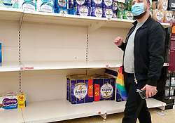 © Licensed to London News Pictures. 28/09/2020. London, UK. A shopper wearing a face mask walks past nearly empty shelves of toilet rolls in Sainsbury's supermarket in London as essential items start to run low amidst a possible second lockdown in London due to a rise in COVID-19 cases. The government is considering a 'total social lockdown' for London and parts of the North if coronavirus infection rates do not fall. Number of supermarkets are restricting shoppers from bulk-buying products such as flour, pasta, toilet rolls and anti-bacterial wipes. Photo credit: Dinendra Haria/LNP