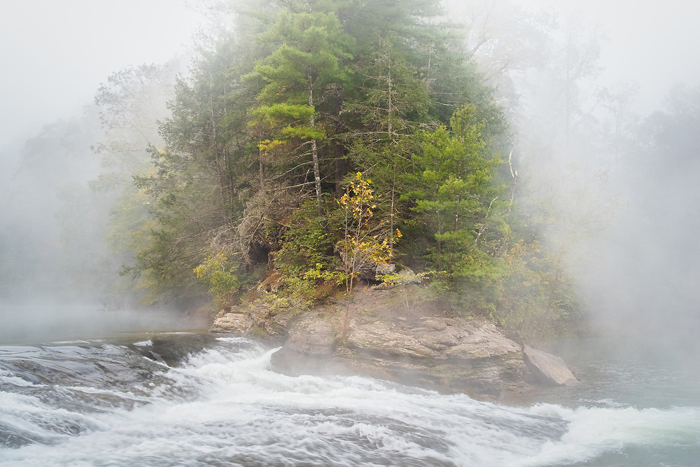 A turbulent scene unfolds around a rocky ledge adorned with evergreens and a lone maple grasping onto the last of its autumn leaves, the stark details clashing with a thick moody fog enveloping the Falls of Falls Mill, West Virginia.