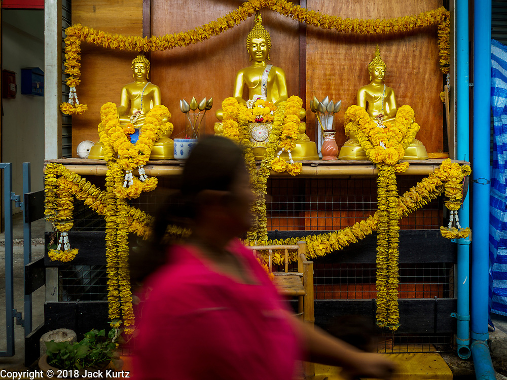 17 SEPTEMBER 2018 - BANGKOK, THAILAND:  A woman walks past a Buddhist shrine in the Klong San market, a small local market next to the ICONSIAM development. ICONSIAM is a mixed-use development on the Thonburi side of the Chao Phraya River. It is expected to open in 2018 and will include two large malls, with more than 520,000 square meters of retail space, an amusement park, two residential towers and a riverside park. It is the first large scale high end development on the Thonburi side of the river and will feature the first Apple Store in Thailand and the first Takashimaya department store in Thailand. Rents for shopkeepers in Klong San market is about 30,000 Thai Baht per month (about $920US) and some in Bangkok are concerned that Klong San Market will lose its local character when the huge mall opens.     PHOTO BY JACK KURTZ