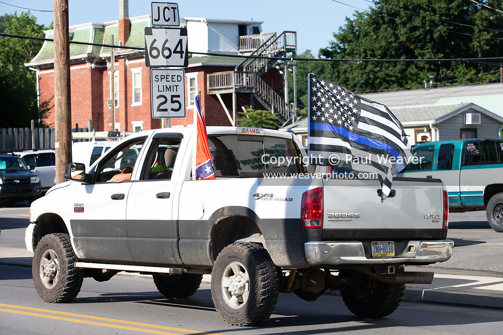 A pick up truck with a confederate flag and a blue lives matter flag passes by the Black Lives Matter protest in Lock Haven, PA.