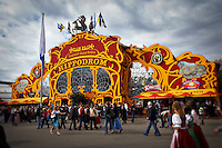 A crowd of people walking around outside the large, colorful, red and yellow Hippodrome Tent at Oktoberfest in Munich, Germany