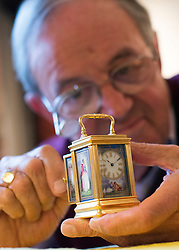 """© Licensed to London News Pictures. 23/10/2014. Guildford, UK. Michael Tooke changes the time on one of the smallest clocks on the premises, a miniature French porcelain panel carriage clock from 1880 made by Drocourt. . As British Summer Time comes to an end, staff at Horological Workshops start the task of changing the 100's of clocks at their store in Guildford, Surrey, UK. Michael Tooke who has owned the store for over 40 years and worked in the clock business all his life said. """"at this time of year we get a lot of people who bring clocks in for repair after they have changed the time incorrectly by winding back the hands manually"""". Clocks change on Sunday morning 26th October. Photo credit : Stephen Simpson/LNP"""