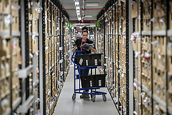 Embargoed to 0001 Friday November 16 A worker picks and scans clothing from thousands of clothing racks at Amazon's fulfillment centre in Swansea, in the run up to Black Friday.