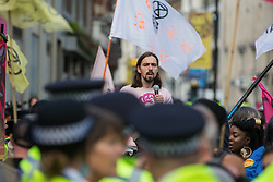 London, UK. 23rd August, 2021. An Extinction Rebellion activist observes Metropolitan Police officers asking activists to move out of a road in the Covent Garden area during the first day of Impossible Rebellion protests. Extinction Rebellion are calling on the UK government to cease all new fossil fuel investment with immediate effect. Credit: Mark Kerrison/Alamy Live News