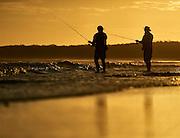Beach fishing at sunset, & Mile beach, Gerroa, South Coast, NSW, Australia
