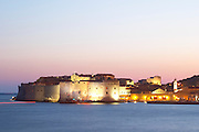 View over the Old Town in the evening after sunset, the city lights glimmering, the sky deep blue and orange pink, deep blue sea, view of the Saint John's Fort and the old harbour from the luxury Excelsior Hotel and Spa restaurant terrace Dubrovnik, old city. Dalmatian Coast, Croatia, Europe.