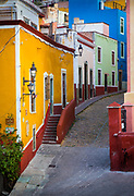Typical colorful street in Guanajuato, Mexico with its Spanish colonial buildings.<br /> ------<br /> Guanajuato is a city and municipality in central Mexico and the capital of the state of the same name. It is part of the macroregion of Bajío. It is in a narrow valley, which makes its streets narrow and winding. Most are alleys that cars cannot pass through, and some are long sets of stairs up the mountainsides. Many of the city's thoroughfares are partially or fully underground. The historic center has numerous small plazas and colonial-era mansions, churches and civil constructions built using pink or green sandstone.<br /> <br /> The origin and growth of Guanajuato resulted from the discovery of minerals in the mountains surrounding it. The mines were so rich that the city was one of the most influential during the colonial period. One of the mines, La Valenciana, accounted for two-thirds of the world's silver production at the height of its production.<br /> <br /> The city is home to the Mummy Museum, which contains naturally mummified bodies that were found in the municipal cemetery between the mid 19th and 20th centuries. It is also home to the Festival Internacional Cervantino, which invites artists and performers from all over the world as well as Mexico. Guanajuato was the site of the first battle of the Mexican War of Independence between insurgent and royalist troops at the Alhóndiga de Granaditas. The city was named a World Heritage Site in 1988.