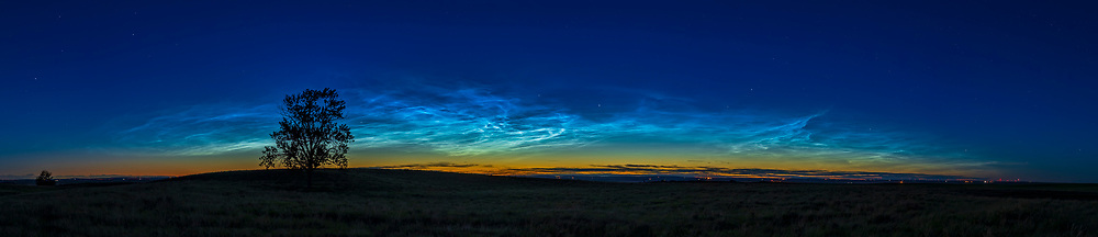 """A 90° panorama of the massive """"grand display"""" of noctilucent clouds at dusk on June 16, 2021 from """"One Tree Hill"""" near home in southern Alberta. This display was bright and extensive at dusk on June 16, and re-appeared over much of the northeastern sky at dawn on June 17. This shows the arc of the NLCs, defined at the top by the edge where sunlight is no longer illuminating the clouds, an edge that drops in altitude as the Sun itself drops farther below the horizon. Capella is at centre, Leo and Regulus at far left, and Perseus at right of centre.<br /> <br /> The main colour of NLCs is electric blue, very much so this night when they were so bright. <br /> <br /> This is a panorama of 10 segments with the 50mm Sigma lens and Canon R6, stitched with Adobe Camera Raw."""