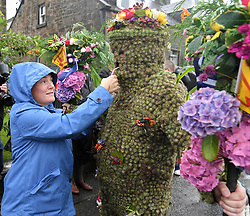 Pictured: Burryman Andrew Taylor get's his first whisky of the day from a local wellwisher.<br /> <br /> The folklore character the Burryman carried out his annual walk through the streets of Queensferry to mark the start of the Ferry Fair, traditionally having a glass of whisky at every bar on the route. Covered head to toe in over 20,000 burrs, the tradition dates back hundreds of years.<br /> <br /> © Dave Johnston / EEm