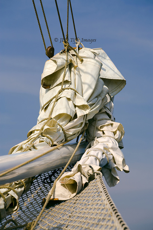 White canvas sail furled and folded around the bowsprit of a sailing vessel makes an abstract fabric sculpture in the complexity of its folds.  Above, clear blue sky and below part of the bowsprit net make a background that sets it off.