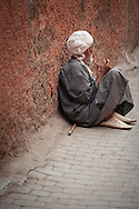 Old man resting in one of streets near the Djemaa El-Fna Medina, Marrakech, Morocco