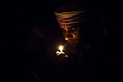 A young Bedouin man lights a cigarette with a lighter at night at a desert camp in Wadi Rum, Jordan.