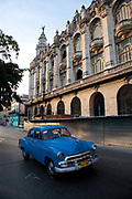 An old Amercian car zooms drives past the National Theatre, Teatro Nacional in Havana.