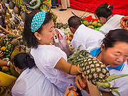 30 OCTOBER 2014 - BANGKOK, THAILAND: People pick up fresh fruit that has been placed during the parade marking the start of the annual temple fair at Wat Saket. Wat Saket is on a man-made hill in the historic section of Bangkok. The temple has golden spire that is 260 feet high which was the highest point in Bangkok for more than 100 years. The temple construction began in the 1800s in the reign of King Rama III and was completed in the reign of King Rama IV. The annual temple fair is held on the 12th lunar month, for nine days around the November full moon. During the fair a red cloth (reminiscent of a monk's robe) is placed around the Golden Mount while the temple grounds hosts Thai traditional theatre, food stalls and traditional shows.   PHOTO BY JACK KURTZ