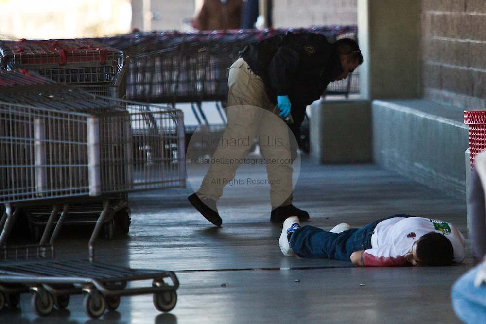 Investigators check the body of a shopper killed in drug related violence at the Costco in Juarez, Mexico January 15, 2009. The shooting, believed linked to the ongoing drug war which has already claimed more than 40 people since the start of the year. More than 1600 people were killed in Juarez in 2008, making Juarez the most violent city in Mexico.    (Photo by Richard Ellis)