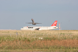 An American Airlines Jet Flies over a NWA Jet as it taxis on the runway