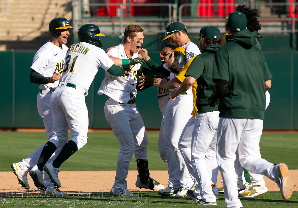 Sep 26, 2021; Oakland, California, USA; Oakland Athletics left fielder Mark Canha (20) is mobbed by his teammates after hitting a game-winning single against the Houston Astros in the ninth inning at RingCentral Coliseum. Mandatory Credit: D. Ross Cameron-USA TODAY Sports