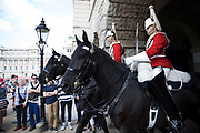 Tourists watch from Horse Guards Parade during the Changing of the Guard in London, England, United Kingdom.