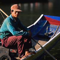 Fisherman poses in boat, Ban Pak Ou, Luang Phrabang, Laos