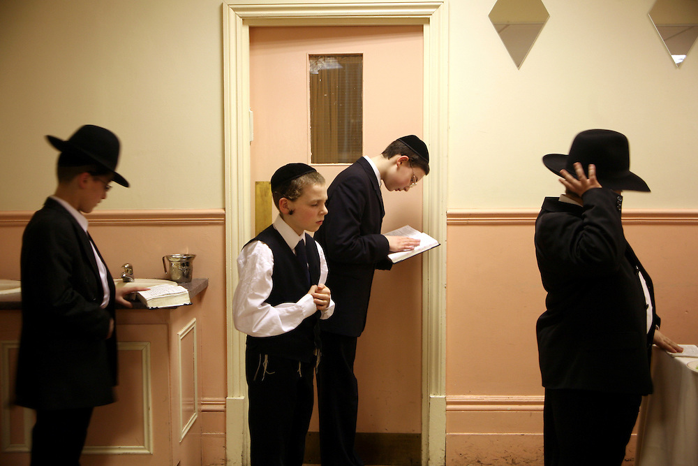 Friends of a 13 year-old Orthodox Jewish boy who have already had their Bar Mitzvah pray without him before his begins, Stamford Hill. The Bar Mitzvah signals the coming of age for a young Jewish boy, they become responsible to observe the commandments of the Torah. It coincides with physical puberty and they begin to participate in all areas of Jewish life. A Bar mitzvah ceremony is a big occasion, the young boy reads a section from the Torah to his family and friends and a mitzvah meal is consumed.