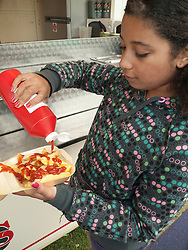 Girl putting ketchup onto a tray of chips
