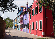 """Brightly painted blue, pink, purple, red, and orange houses. Burano, known for knitted lacework, fishing, and colorfully painted houses, is a small archipelago of four islands linked by bridges in the Venetian Lagoon, in the Veneto region of Italy, Europe. Burano's traditional house colors are strictly regulated by government. The Romans may have been first to settle Burano. Romantic Venice (Venezia), """"City of Canals,"""" stretches across 100+ small islands in the marshy Venetian Lagoon along the Adriatic Sea in northeast Italy, between the mouths of the Po and Piave Rivers. Venice and the Venetian Lagoon are honored on UNESCO's World Heritage List."""