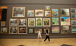 © licensed to London News Pictures. LONDON, UK  02/06/11. Vistors to the Royal Academy of the Arts Summer Exhibition walk past a wall of paintings. The Royal Academy of the Arts Summer Exhibition is the largest open contemporary art exhibition in the world, with pieces contributed by established, unknown and emerging artists. Please see special instructions for usage rates. Photo credit should read Matt Cetti-Roberts/LNP