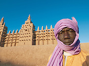 A man outside the Great Mosque of Djenné, the worlds largest mud built structure and UNESCO heritage site, early in the morning at Djenné, Mali