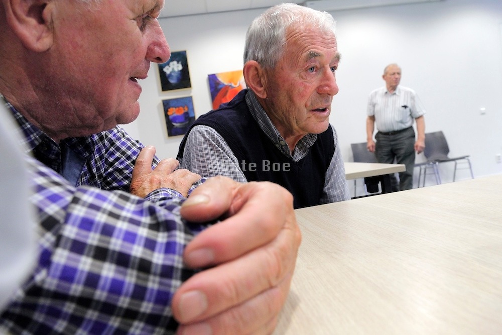 two men talking at a recreational senior indoors sport club meeting up