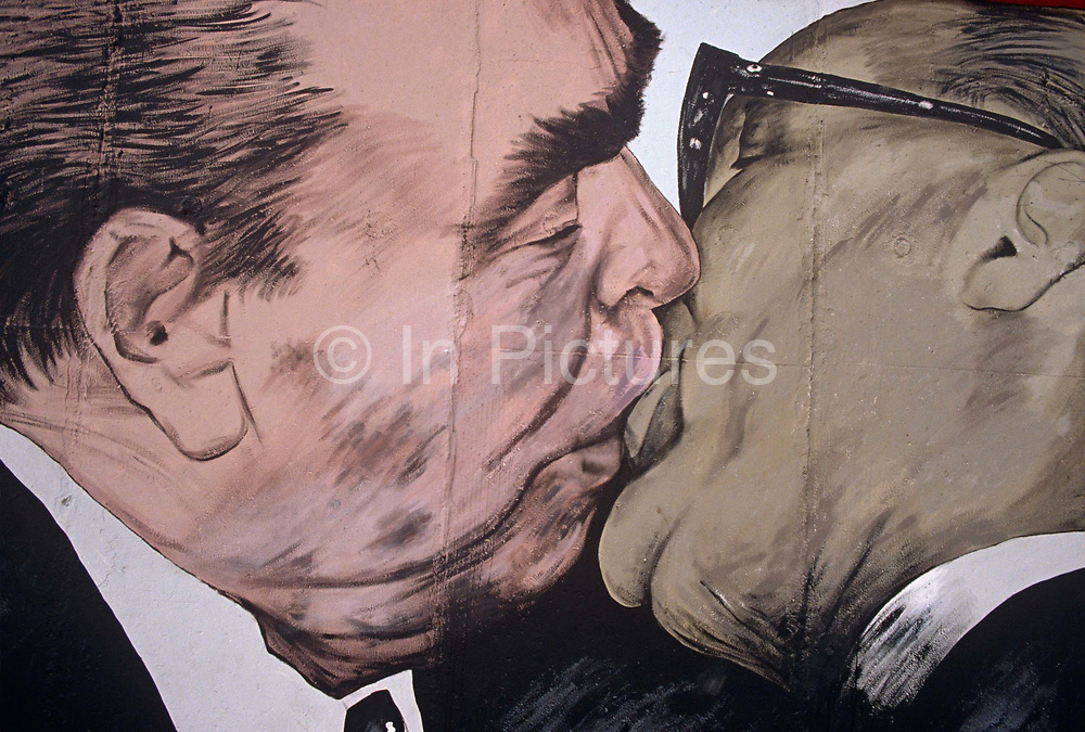 A detail from the oversized artwork entitled Brotherhood Kiss (Bruderkuss) by Dmitry Vrubel that once adorned a section of the notorious Berlin Wall in western Germany Russian. Two seemingly gay men are kissing on the lips but this is one of the most famous paintings – a symbol of a divided Europe during the Cold War. It shows Communist Soviet leader Leonid Brezhnev kissing his East German (DDR) counterpart Erich Honecker, which was ultimately copied on to coffee cups and T-shirts across the world before being destroyed by the authorities. The artist was angry but he says he will paint a new image which was derived from a photograph of the two leaders taken 1979 but became a potent symbol of Communism's corruption and ultimate failure.