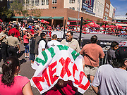 16 SEPTEMBER 2012 - PHOENIX, AZ:  A woman uses a Viva Mexico banner for shade before the Lucha Libre wrestling show in Phoenix. The Arizona Diamondbacks hosted their 14th Annual Hispanic Heritage Day, Sunday to kick off Hispanic Heritage Month (Sept. 15-Oct. 15) before the 1:10 p.m. game between the D-backs and San Francisco Giants. The main attraction of the Day was three Lucha Libre USA exhibition wrestling matches in front of Chase Field stadium before the game.   PHOTO BY JACK KURTZ