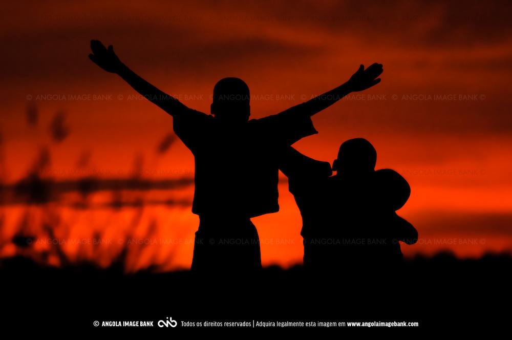 Siluetas de crianças ao pôr do sol perto do Porto Amboim. Província do Kwanza Sul. Angola