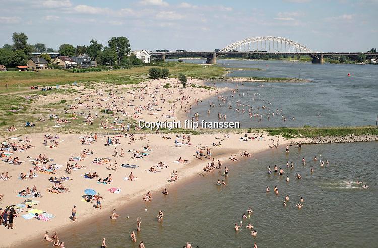 Nederland, nijmegen, 25-6-2020Mensen trekken massaal naar de oevers van de waal en de spiegelwaal in het rivierpark aan de overkant van Nijmegen . De warmte, hoge temeratuur,  drijft mensen naar het water  . Het is verboden in de rivier te zwemmen vanwege de stroming het het drukke scheepvaartverkeer .  . Foto: Flip Franssen