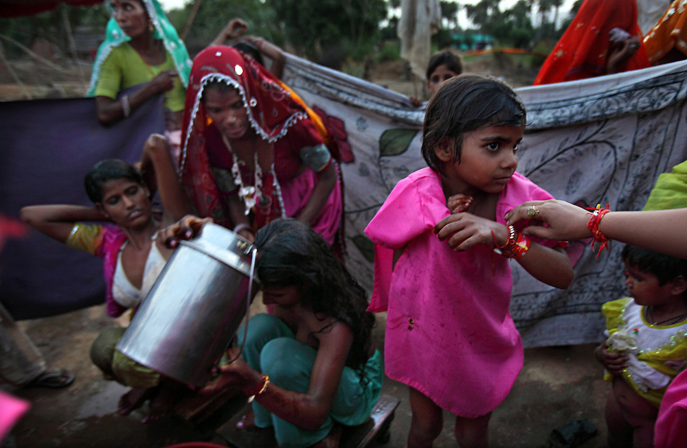 Rajni, 5, bathes with her other two siblings the afternoon of their wedding, Rajasthan, India, April 27, 2009. Three young sisters Radha, 15, Gora, 13, and Rajni, 5, were married to their young grooms Aleen, Giniaj and Kaushal, who were also siblings, on the Hindu holy day of Akshaya Tritiya, called Akha Teej in north India. The auspicious day is said to bring good luck to couples married then and is widely known in Rajasthan as the day most child marriages occur. Despite legislation forbidding child marriage in India, such as the Child Marriage Restraint Act-1929 and the much more progressive Prohibition of Child Marriage Act of 2006, marrying children off at a very tender age continues to be accepted by large sections of society.
