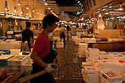 A worker pulls a cart past wholesalers` stalls at Tsukiji wholesale fish market in Tokyo, Japan. July 15th 2008