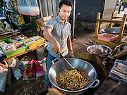 30 DECEMBER 2015 - BANGKOK, THAILAND:  A snack vendor fries peanuts in Bang Chak Market. The market is supposed to close permanently on Dec 31, 2015. The Bang Chak Market serves the community around Sois 91-97 on Sukhumvit Road in the Bangkok suburbs. About half of the market has been torn down. Bangkok city authorities put up notices in late November that the market would be closed by January 1, 2016 and redevelopment would start shortly after that. Market vendors said condominiums are being built on the land.           PHOTO BY JACK KURTZ
