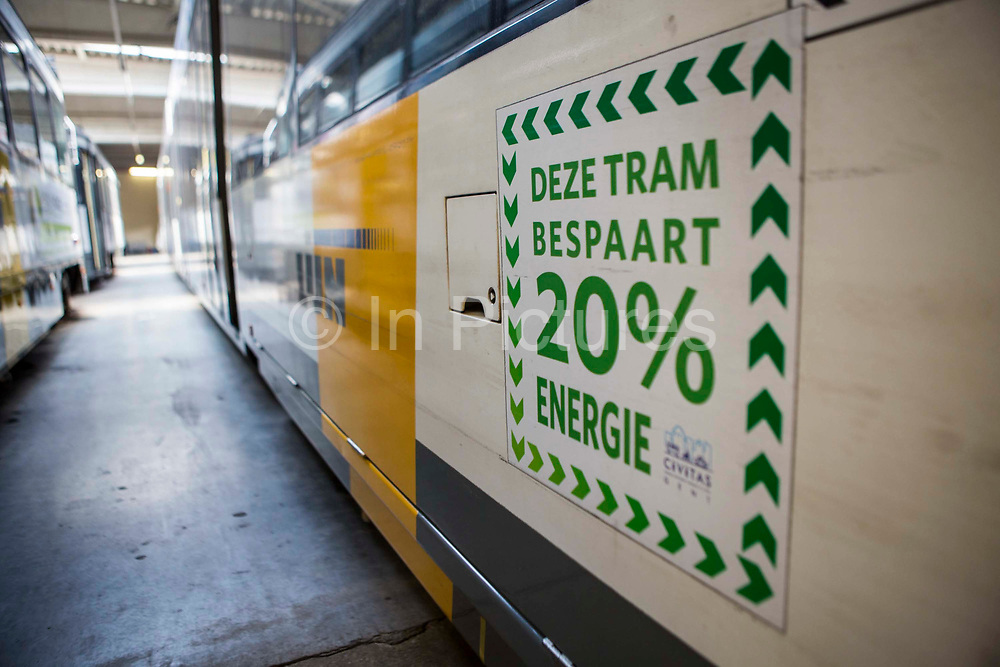 A poster sticker on the side of a De Lijn modern electric tram which uses 20% less energy than the older model of tramcar.