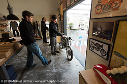 Harley-Davidson's (L>R) Charlie Wartgow, head of design Ray Drea and Ben McGinley check out the Deus Ex Machina new Tokyo store 3-days after its grand opening. Tokyo. Japan. Wednesday, December 10, 2014. Photograph ©2014 Michael Lichter.