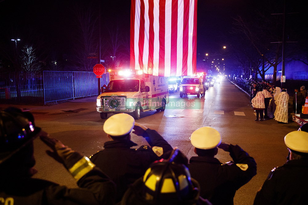 December 18, 2018 - Chicago, Illinois, USA - Members of the Chicago Fire and Police departments salute as the bodies of two officers who were killed Monday night while pursuing a suspect and struck by a South Shore train near 103rd Street and Dauphin Avenue arrive at the medical examiner's office in Chicago, Ill. (Credit Image: © Armando L. Sanchez/Chicago Tribune/TNS via ZUMA Wire)