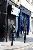Woman looking into shop window through shutters, Dublin, Ireland
