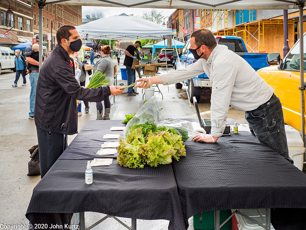 """23 MAY 2020 - AMES, IOWA: JASON JONES, right, observes """"social distancing"""" guidelines while he sells salad greens to a customer at his stand at the Farmers' Market in downtown Ames. Jones grows his greens on a farms in Maxwell, IA. He said it felt """"really good"""" to be able to reopen his market stand. The Ames Main Street Farmers' Market reopened Saturday after nearly a month of only online sales because of Iowa's bans on large gatherings caused by the COVID-19 pandemic. Only about 15 venders set up stalls Saturday and attendance was significantly lower than normal. All of the venders wore face masks and many, but not all, of the shoppers wore face masks. Farmers' markets are popular community gatherings in Iowa, but they've been on hiatus since the Coronavirus (SARS-CoV-2) pandemic. At this time, Iowa farmers' markets are not allowed to have entertainment or sell non-food or non-agricultural goods.         PHOTO BY JACK KURTZ"""