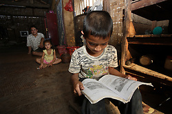 La has plenty of homework to complete after school, he can sit anywhere with his books, Vang Mak primary school, Vieng thong district, Bolikhamxai Province, Lao PDR