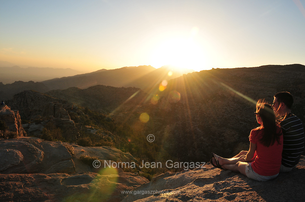 Visitors to flock to Windy Point Vista on Mount Lemmon, Tucson, Arizona, USA, to watch the sun set and the full moon rise.  The vista is about midpoint along the Catalina Highway in the Santa Catalina Mountains of the Coronado National Forest on a Sky Island in the Sonoran Desert.