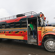 Departing chicken bus behind the Mercado Municipal (town market) in Antigua, Guatemala. From this extensive central bus interchange the routes radiate out across Guatemala. Often brightly painted, the chicken buses are retrofitted American school buses and provide a cheap mode of transport throughout the country.