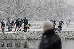 © Licensed to London News Pictures. 24/01/2021. London, UK. Members of the public go out in the snow on Wimbledon Common in blizzard like conditions as the temperature dropped to lows of -5 in South West London this morning. A chilly day ahead is forecast for the South East with the Met Office issuing a yellow weather warning for snow today with disruption to travel as the cold weather continues. Photo credit: Alex Lentati/LNP