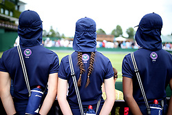 Ball girls and boys stand court side on day three of the Wimbledon Championships at the All England Lawn Tennis and Croquet Club, Wimbledon