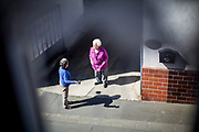 Two neighbours in the pensioner age having a chat in a save social distance.